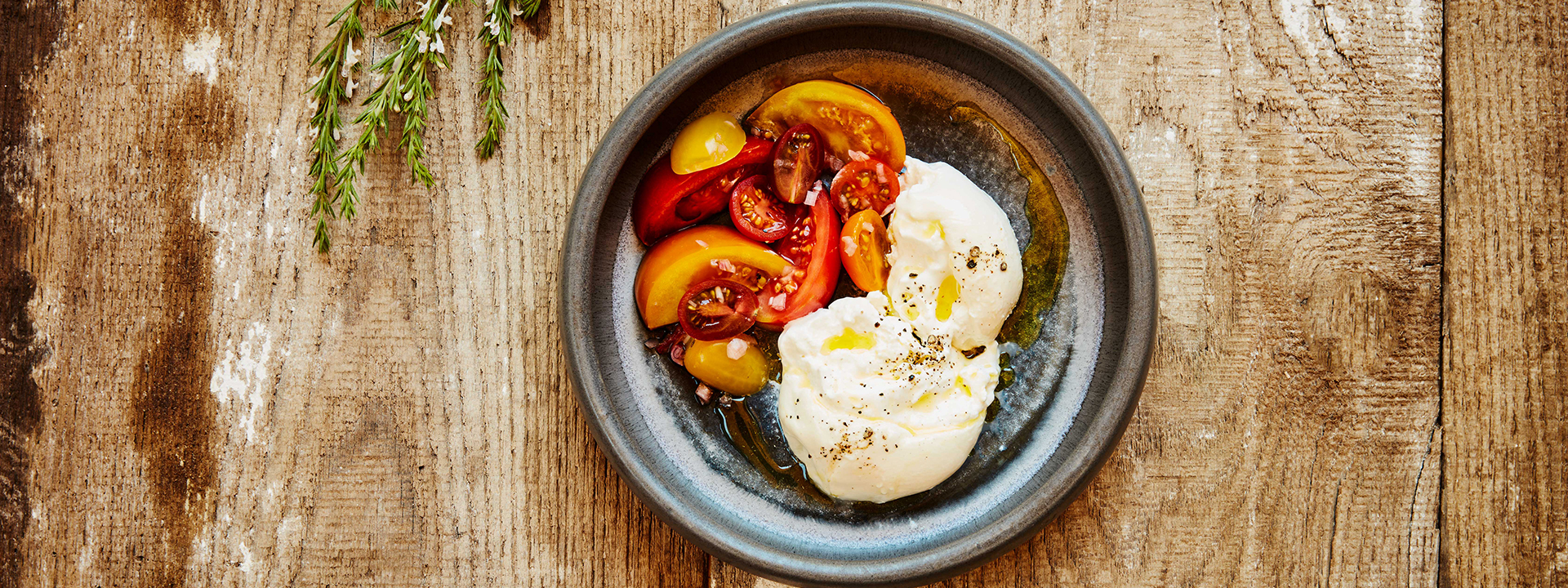 Roasted tomatoes with burrata and garnished with olive oil
