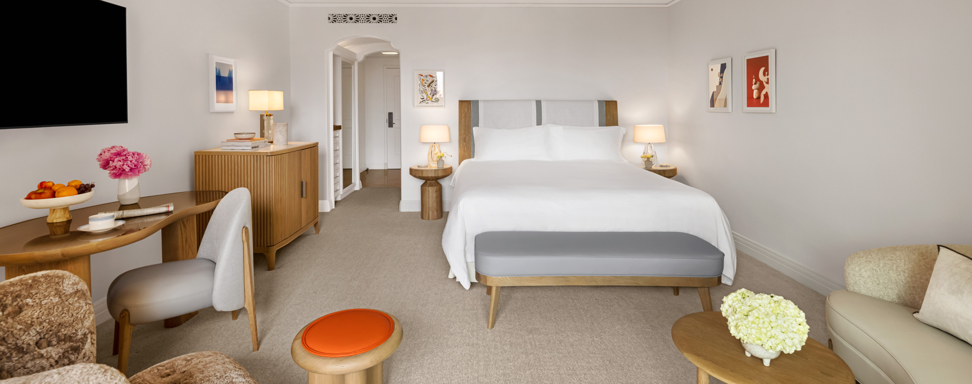 King size bed with orange stool, a television and pink fresh flowers in Maybourne Balcony Room