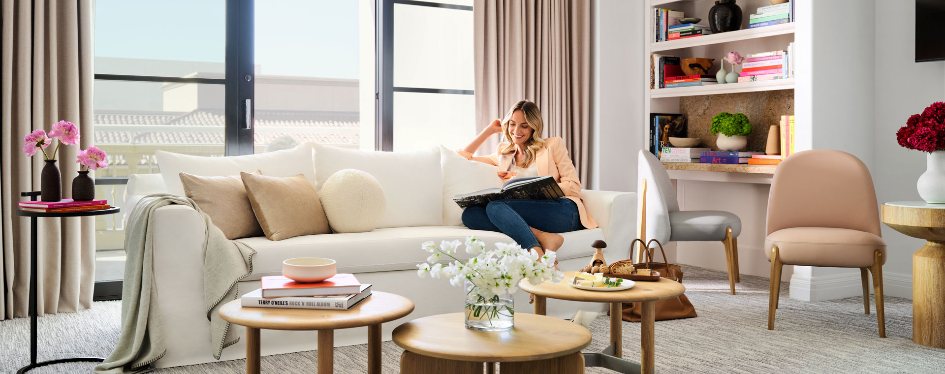 Woman sitting on couch in a suite by a coffee table reading a book