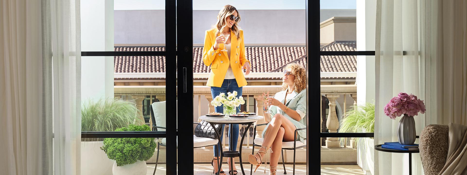 Two women enjoying drinks on the luxury suite balcony